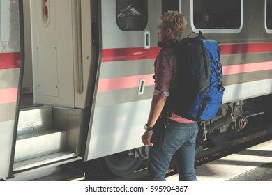 Young tourist with luggage waiting for a train at railway station. Travel concept