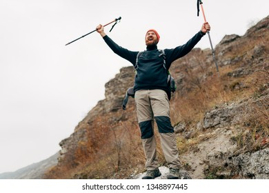 Young tourist male hiking in mountains, finished his track, feels happy. Ttraveler bearded man trekking and mountaineering during his journey. Travel, people, sport and healthy lifestyle concept