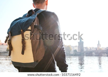 cd97ee0a357b A young tourist man with a backpack stands next to the river Vltava in Prague  and