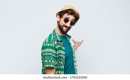 young tourist man feeling happy and cheerful, smiling and welcoming you, inviting you in with a friendly gesture against white wall