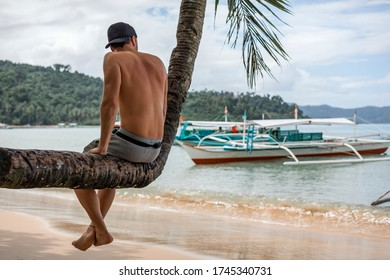 A young tourist man sitting on a bent palm tree next to the beach in Port Barton, Palawan, Philippines (rare view)