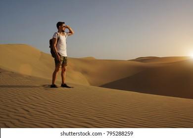 Young tourist man walking throw the desert.