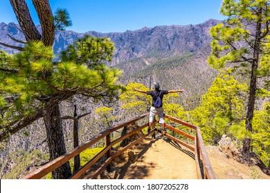 A young tourist at the Mirador Lomo de las Chozas de La Cumbrecita on the island of La Palma next to the Caldera de Taburiente, Canary Islands. Spain