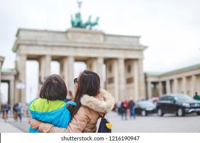 Young tourist mother with her little son looking at Brandenburg gate and telling him some history about the city.Happy family travel concept