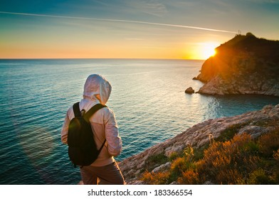 Young tourist on a hill enjoying the sunset on the sea