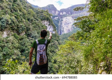 Young tourist pointing with finger on the Gocta waterfall Gocta Waterfall/ Chachapoyas/ Peru/ south america