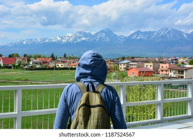 Young tourist in Poprad city looking at High Tatras mountains. Erasmus student traveling with backpack