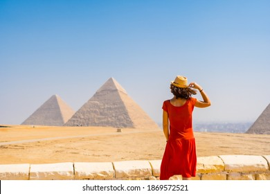 A young tourist in a red dress looking at the Pyramids of Giza, the oldest Funerary monument in the world. In the city of Cairo, Egypt