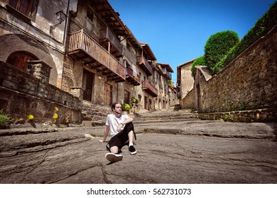 Young tourist resting on an old street in medieval town Rupit, Catalonia, Spain