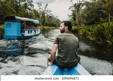Young tourist sailing on a wooden boat for a beautiful river in the borneo jungle, in Kalimantan. Excursion to see the island's wildlife. Travel Photography.