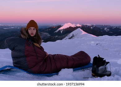 Young tourist, sitting alone in sleeping bag, enjoying beautiful snowy mountain view on clear sunny winter morning. Tourism and active lifestyle concept.