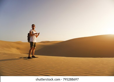 Young  tourist standing with his smartphone in a middle of a desert.