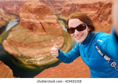 Young tourist taking a photo of herself by famous Horseshoe Bend, Arizona, USA