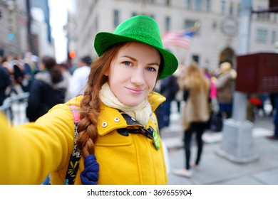 Young tourist taking a selfie with her smartphone during the annual St. Patrick's Day Parade on 5th Avenue in New York City