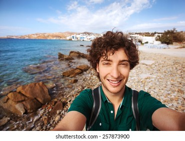 Young tourist taking selfie on Mykonos beach with Little Venice in the background. Mykonos, Greece.
