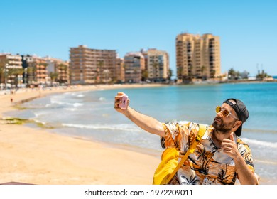 A young tourist taking a selfie at Playa del Cura in the coastal city of Torrevieja, Alicante, Valencian Community. Spain, Mediterranean Sea
