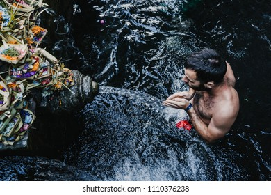 Young tourist visiting the Pura Tirta Temple in Bali, indonesia dressed in a sarong. Doing the ritual in each of the jets of water. Spiritual visit. Travel concept.