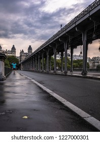 Young tourist walking by Pont de bir hakeim metro bridge paris france paris france during summer with thick cloud covered sky