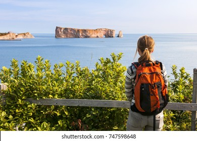 Young tourist woman with backpack enjoying Perce Rock view from  Gaspe Peninsula in Quebec, Canada