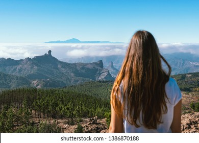 young tourist woman from behind in front of el teide volcano of tenerife on gran canaria, canary islands