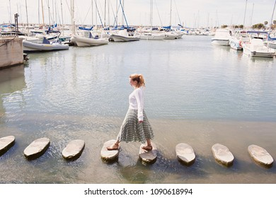 Young tourist woman crossing water stepping stones in yachting boats port coastal destination on holiday, sunny outdoors. Solo traveller, adventure discovery. Healthy leisure recreation lifestyle.