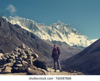 a young tourist woman is engaged in trekking in the highlands of the Himalayas in Nepal among the snowy peaks of mountains and glaciers