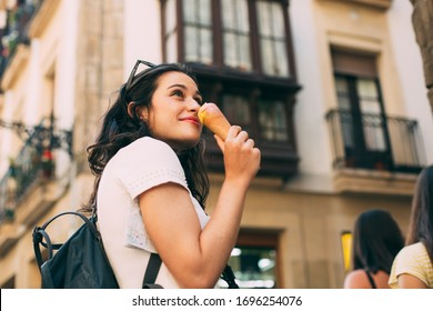 Young tourist woman enjoying and ice cream while visiting an european city