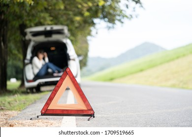 Young tourist woman having broken car, sitting in car and calling for assistance and place red triangle warning sign on the road.