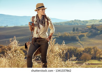 young tourist woman in hiking clothes with bag and retro film photo camera looking aside in the front of scenery of summer Tuscany ,Italy.