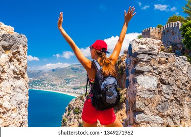 Young tourist woman look at ruins in Alanya peninsula, Antalya district, Turkey, Asia. Famous tourist destination with high mountains. Part of ancient old Castle. Summer bright day