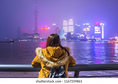 Young tourist woman looking at view of the bund in shanghai, china. Young asian woman in jacket clothes looking at the view of city skyline in shanghai.