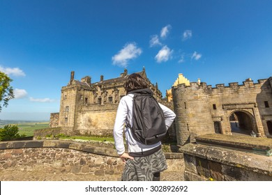 Young tourist woman observes the famous Stirling Castle, in Stirling town, Central Scotland, UK, Europe on a sunny day.