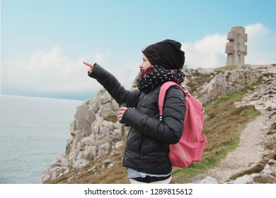 young tourist woman pointing with the finger at something at the crucifix monument at the cape of Pen Hir in France.