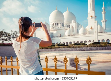 Young tourist woman shooting on mobile phone Sheikh Zayed great white mosque in Abu Dhabi, United Arab Emirates, Persian gulf