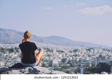 Young tourist woman sitting on top of mountain and looking at a beautiful landscape cityscape Athens Greece. Adult girl tourist relax on hill overlooking Athens in summer. Famous Athens city in Europe