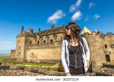 Young tourist woman standing in front of the famous Stirling Castle, in Stirling town, Central Scotland, UK, Europe on a sunny day.
