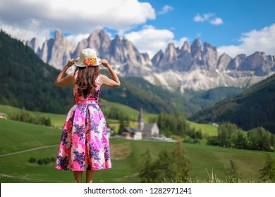 Young tourist Woman standing on the hill Looking to beautiful view of Dolomites mountain peaks and the church of Santa Maddalena on her summer vacation in Italy