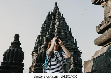 Young tourist woman takin pictures of the amazing Candi Prambanan or Rara Jonggrang, largest Hindu temple site in Indonesia. Yogyakarta, Java. Travel photography.