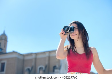 Young tourist woman taking picture with vintage camera outdoor in Rome
