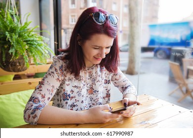 Young tourist woman using smart phone in restaurant waiting for her morning coffee.Tourist Girl texting on the smart phone in a restaurant.