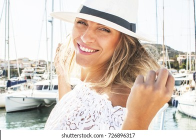 Young tourist woman walking in harbor of small Italian city in white hat