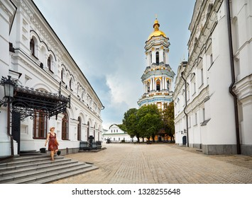 Young tourist woman walking near Bell Tower with golden dome at Kiev Pechersk Lavra Christian complex. Old historical architecture in Kiev, Ukraine
