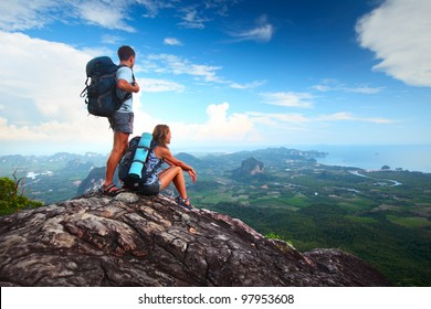 Young tourists with backpacks enjoying valley view from top of a mountain