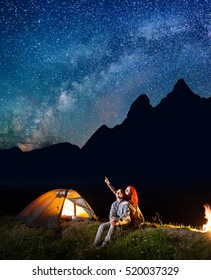 Young tourists man and woman looking at the shines starry sky at night. Happy couple sitting near tent and campfire. Milky way and mountains on the background