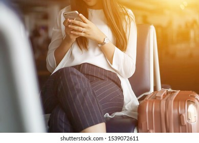 Young tourists Sitting and waiting at the airport With her bag She is playing her mobile phone. selective focus, vintage tone color
