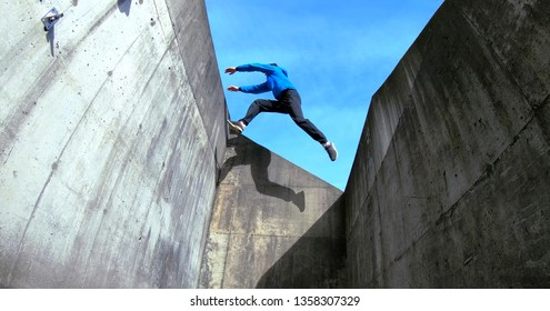young traceur freerunner free runner parkour action sport athlete doing a wall gap jump in stavanger landing in a cat jump from height