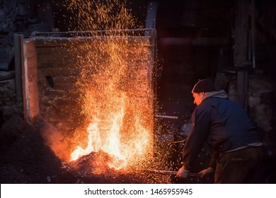 young traditional Blacksmith working with open fire  The blacksmith making flames in smithy with spark fireworks forging hot iron in workshop