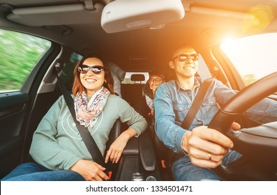 Young traditional family has a long auto journey and Cheerfully singing aloud the favorite song together. Safety riding car concept wide angle inside car view image.