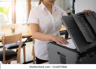 Young trainee female in uniform use printer to scan important and confidential documents in office. Business concept.
