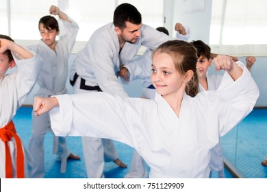 Young trainer is correcting children moves in karate class.